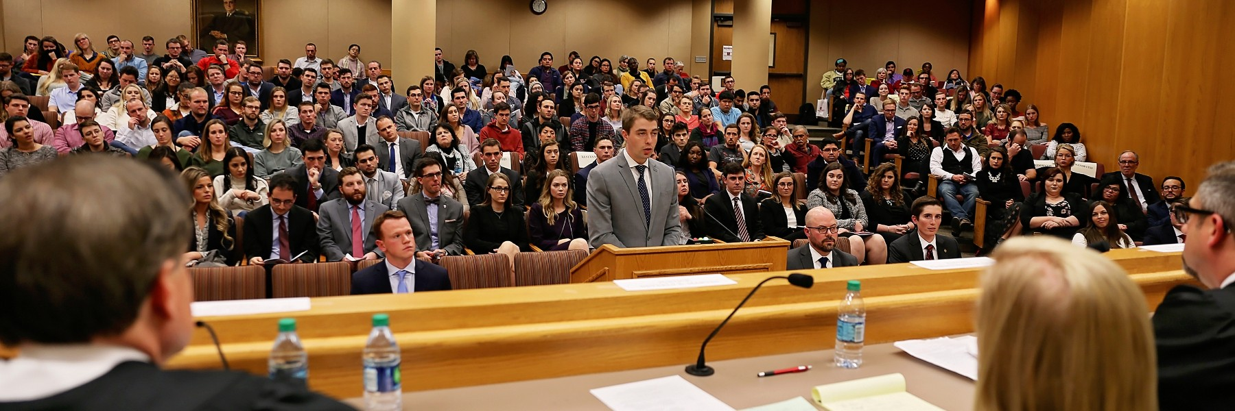 Sherman Minton Moot Court Competition at the Maurer School of Law. A single student in a suit speaks before a panel of judges with a large audience behind him.